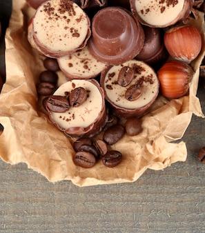 Gustose caramelle al cioccolato con chicchi di caffè e noci su fondo di legno