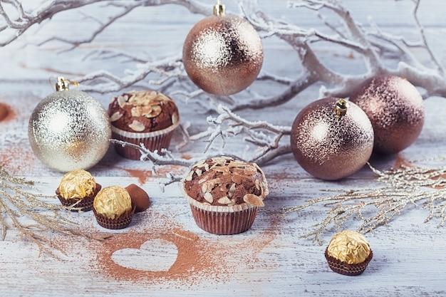Gustoso cupcake al cioccolato con dolci, cacao in polvere a forma di cuore e decorazione invernale su tavola in legno rustico bianco. sfondo vacanza invernale.