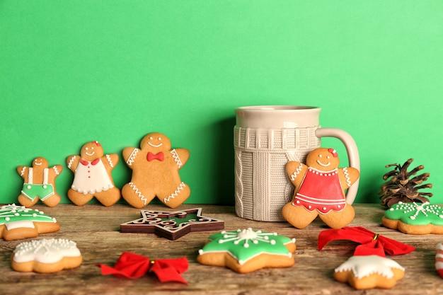 Gustosi biscotti natalizi fatti in casa e tazza su sfondo colorato