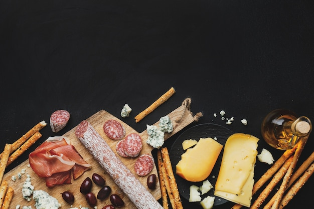 Gustosi antipasti italiani classici su sfondo scuro. vista dall'alto.
