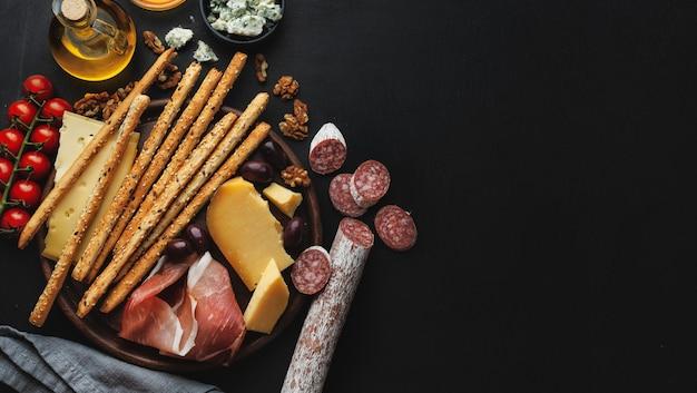 Gustosi antipasti italiani classici sul tavolo scuro. vista dall'alto.