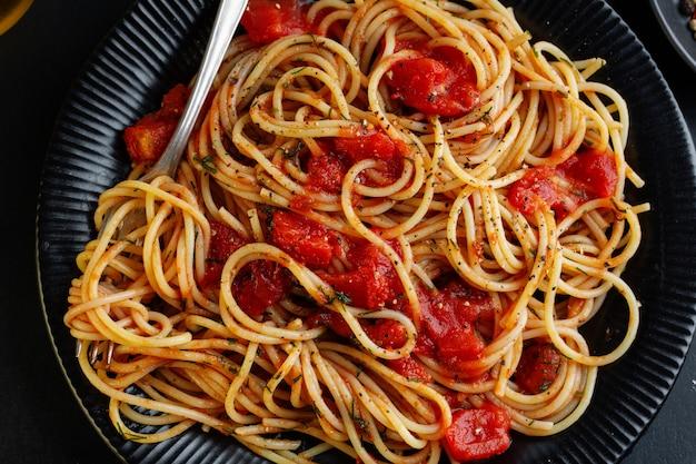 Gustosa pasta italiana classica con salsa di pomodoro e formaggio sul piatto su sfondo scuro. vista dall'alto.