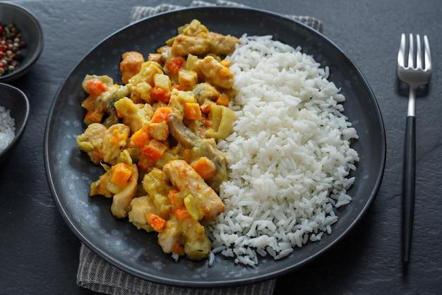 Gustosi bocconcini di pollo autunnali cotti con verdure e riso serviti su un piatto. vista dall'alto