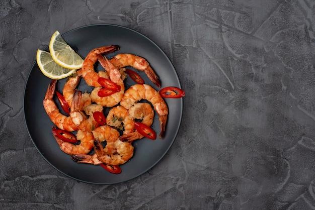 Gustoso gambero fritto con peperoncino e limone. frutti di mare sani. copia spazio. disteso.