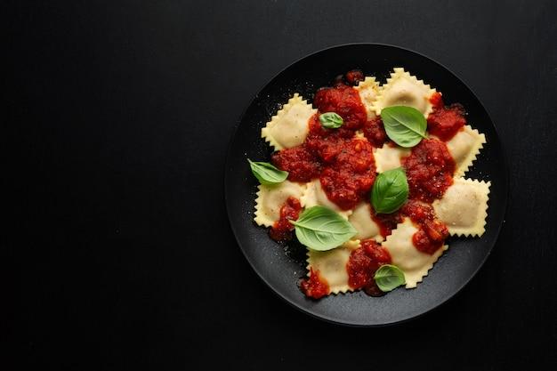 Gustosi ravioli italiani cucinati con salsa di pomodoro e basilico serviti su un piatto scuro.
