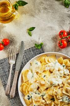 Gustosi ravioli cotti con salsa di panna, pomodorini, olio di semi di girasole e basilico su una superficie di legno chiaro