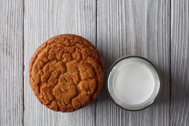Gustosi biscotti e un bicchiere di latte in un vetro trasparente su uno sfondo bianco rustico copia spazio piatto laici