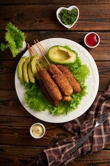 Gustoso cane di mais con salsa e insalata servita sul piatto bianco sulla tavola di legno