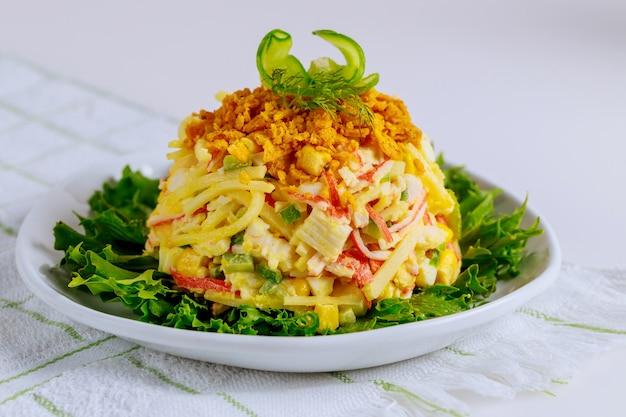 Gustosa insalata di polpa di granchio con mais, cetriolo e uova. avvicinamento.