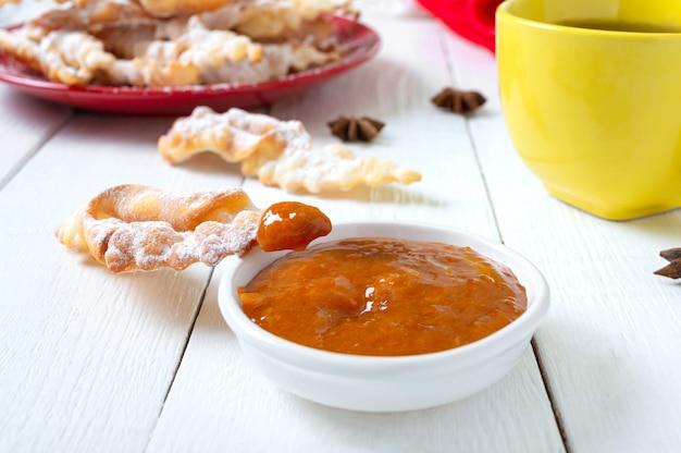 Gustosi biscotti fritti croccanti in zucchero a velo con tè e marmellata a colazione