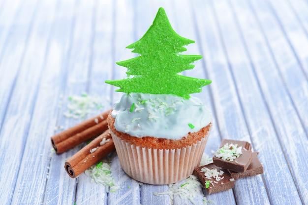 Gustoso cupcake con crema al burro, su fondo in legno colorato