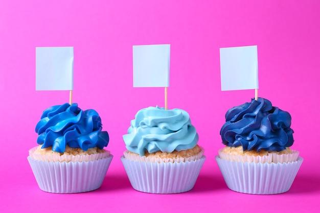 Gustosi cupcakes con tag su sfondo colorato