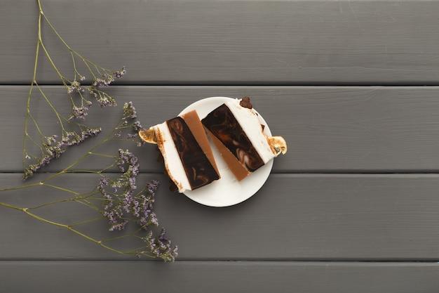 Sfondo gustoso dessert. pezzi di torta al cioccolato su tavolo rustico grigio con fiori viola, stile provenzale, vista dall'alto, spazio copia
