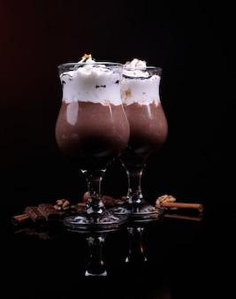 Gustoso dessert con salsa di cioccolato, panna e arancia, isolato su nero