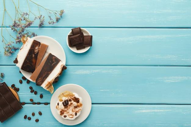 Sfondo di gustosi dessert. varie torte e barrette di cioccolato su tavolo rustico blu con chicchi di caffè sparsi e fiori viola, stile provenzale, vista dall'alto, spazio copia
