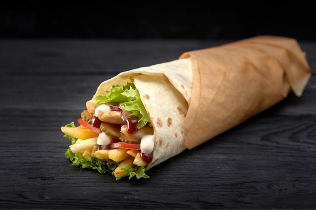 Gustosi spiedini di doner con guarnizioni di insalata fresca e carne arrostita rasata servita in tortilla avvolti su carta marrone come spuntino da asporto