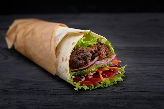 Gustosi spiedini di doner con guarnizioni di insalata fresca e carne arrostita rasata servita in involucri di tortilla su carta marrone come spuntino da asporto