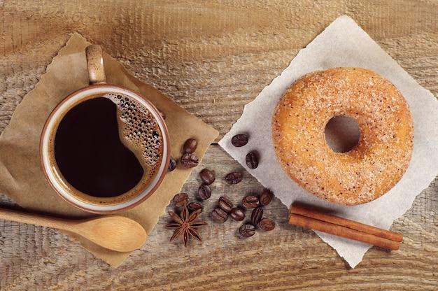 Gustosa ciambella e tazza di caffè caldo sul vecchio tavolo di legno, vista dall'alto