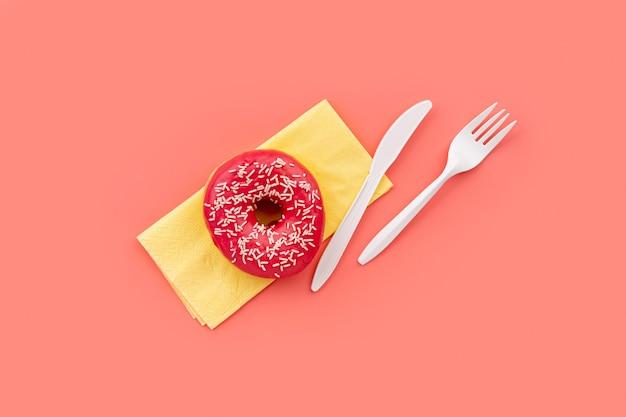 Gustosa ciambella con tovagliolo e posate sul modello di mockup di sfondo rosa per prodotti da forno
