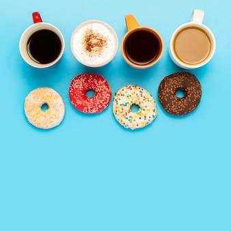Gustose ciambelle e tazze con bevande calde, caffè, cappuccino, tè vista dall'alto