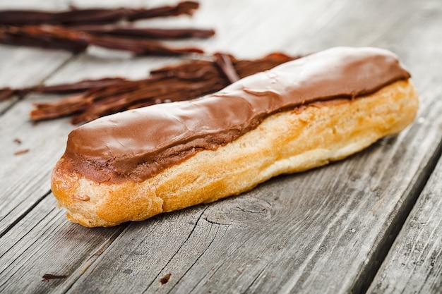 Gustoso eclair con crema al cioccolato sul vecchio tavolo in legno