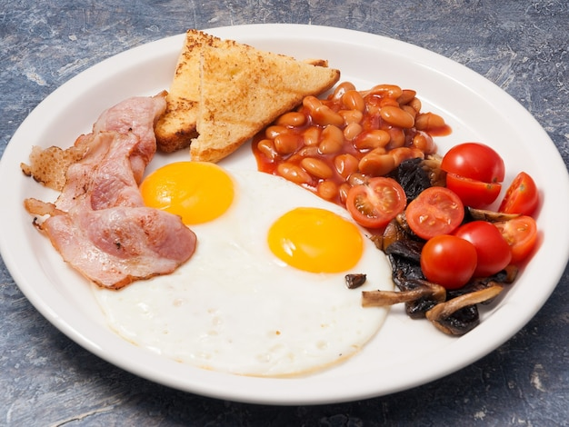 Gustosa colazione inglese: uova, fagioli, pancetta e funghi tostati