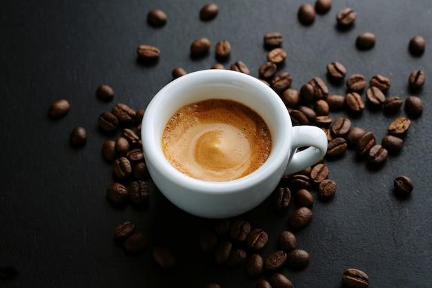 Gustoso caffè espresso servito in tazza con chicchi di caffè intorno e cucchiaio. avvicinamento. sfondo scuro.
