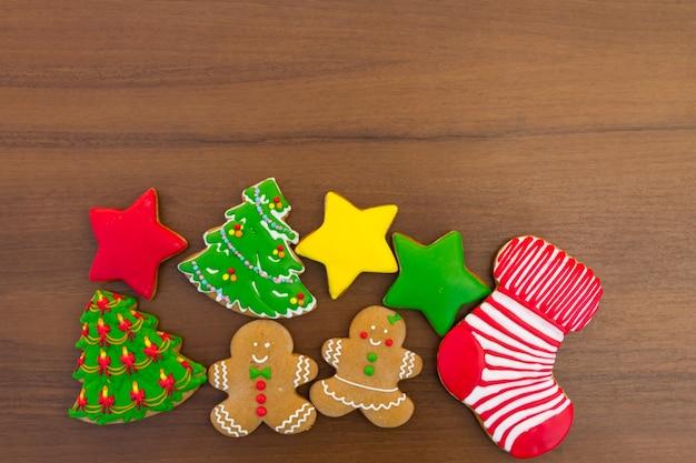Gustosi biscotti natalizi festivi a forma di albero di natale, omino di pan di zenzero, stella e calzino di natale su un tavolo di legno. vista dall'alto