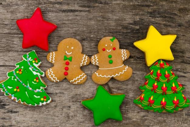 Gustosi biscotti natalizi festivi a forma di albero di natale, omino di pan di zenzero e stelle su tavola in legno rustico. vista dall'alto