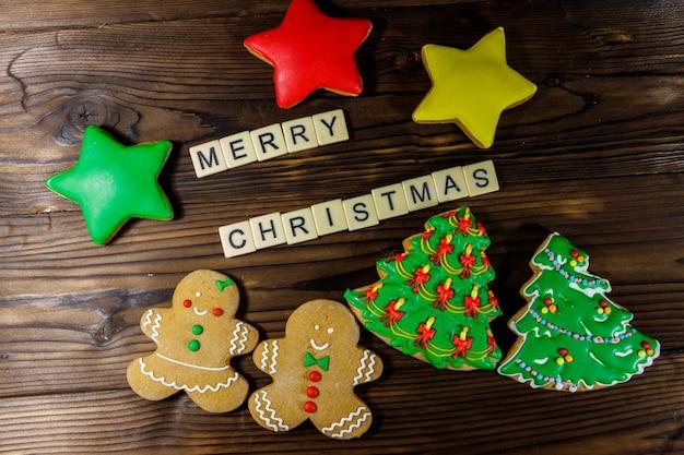 Gustosi biscotti di pan di zenzero natalizio festivo e iscrizione di buon natale sul tavolo di legno. vista dall'alto