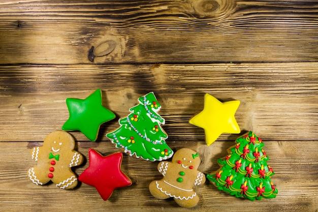 Gustosi biscotti di panpepato natalizio a forma di albero di natale, omino di pan di zenzero, stella e calzino di natale sul tavolo di legno. vista dall'alto