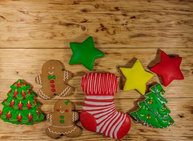 Gustosi biscotti di panpepato natalizio a forma di albero di natale, omino di pan di zenzero, stella e calza di natale sul tavolo di legno. vista dall'alto