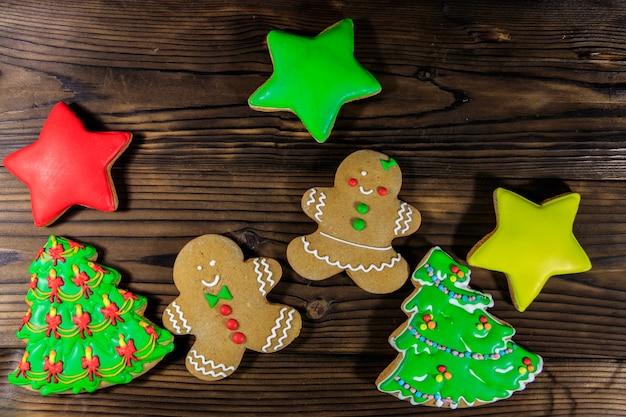 Gustosi biscotti di panpepato natalizio a forma di albero di natale, uomini di panpepato e stelle su un tavolo di legno. vista dall'alto