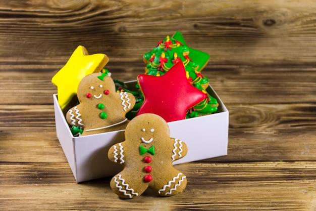 Gustosi biscotti di pan di zenzero natalizi a forma di albero di natale, stelle, uomo di pan di zenzero e donna in scatola su tavola di legno