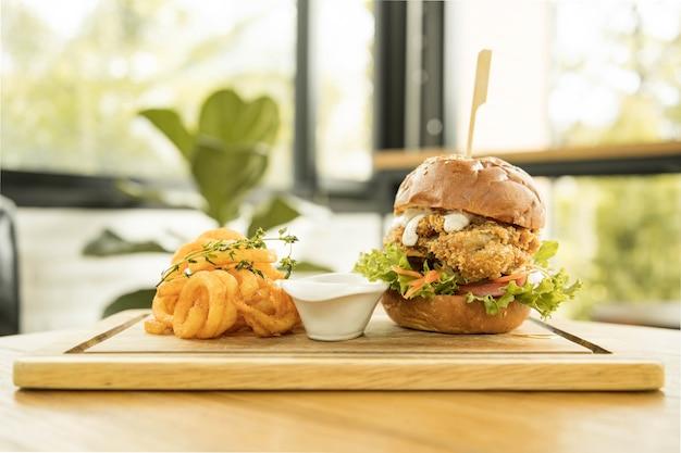 Gustoso pollo infornato con salsa di rucola e maionese servito su tavola di legno, pollo cotto cheese burger con patatine fritte ricci piccanti