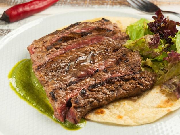 Gustosa bistecca di fianco su tortilla di mais con salsa di spinaci