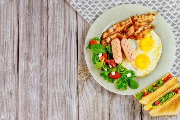 Gustoso cibo per colazione uova, pancetta, insalata e sandwich di formaggio grigliato.