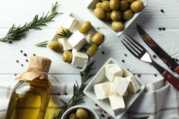 Cibo gustoso con formaggio feta su superficie di legno bianca