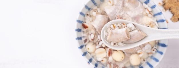 Gustosa zuppa di erbe aromatiche ai quattro tonici, cibo tradizionale taiwanese con erbe aromatiche, intestini di maiale su tavolo di legno bianco, primo piano, piatto, vista dall'alto.