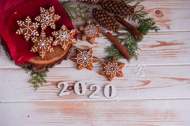 Gustosi e profumati biscotti al cioccolato sono schiacciati con zucchero a velo, con luci multicolori sul tavolo. buon natale