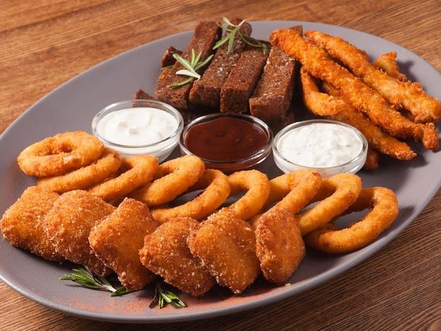 Gustose patatine fritte per birra: anelli di cipolla, crocchette, bastoncini di formaggio, crostini all'aglio