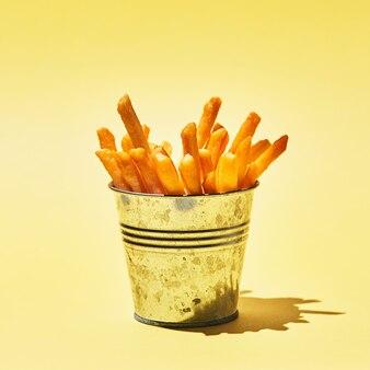 Gustose patatine fritte nel secchio di metallo sul tavolo giallo alla luce del sole.
