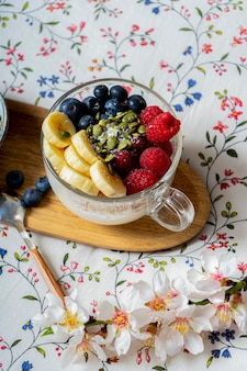 Gustosa colazione fresca a letto sulla tavola di legno. yogurt alla frutta. interno bianco vintage