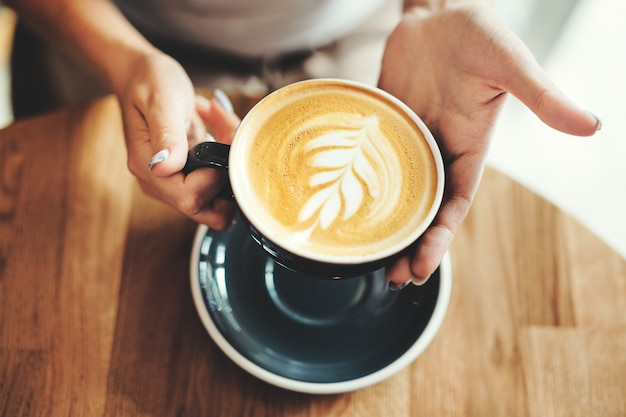 Cappuccino fresco saporito in tazza sulla tavola di legno. donna irriconoscibile che tiene la tazza in mano.