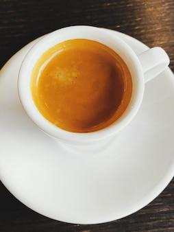 Gustoso caffè espresso italiano fresco in tazza di ceramica bianca sul tavolo nella caffetteria