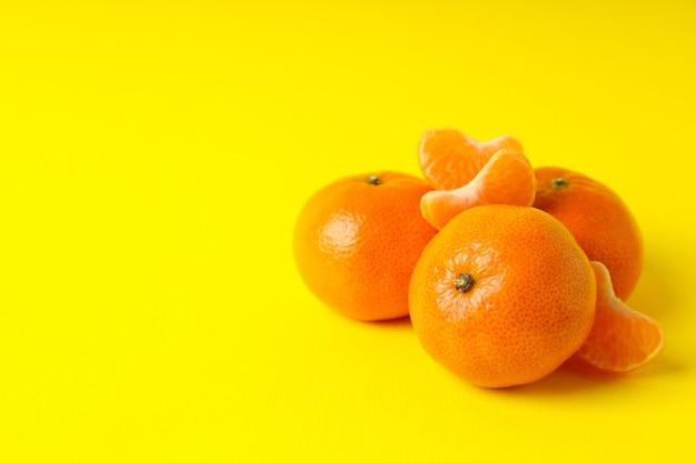 Gustosi mandarini freschi su sfondo giallo, spazio per il testo