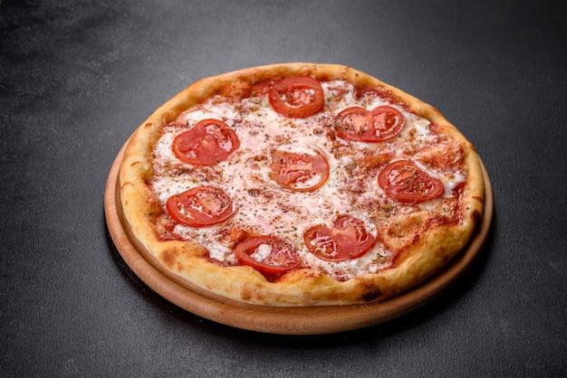 Gustosa pizza fresca al forno con pomodoro, formaggio e basilico su uno sfondo concreto