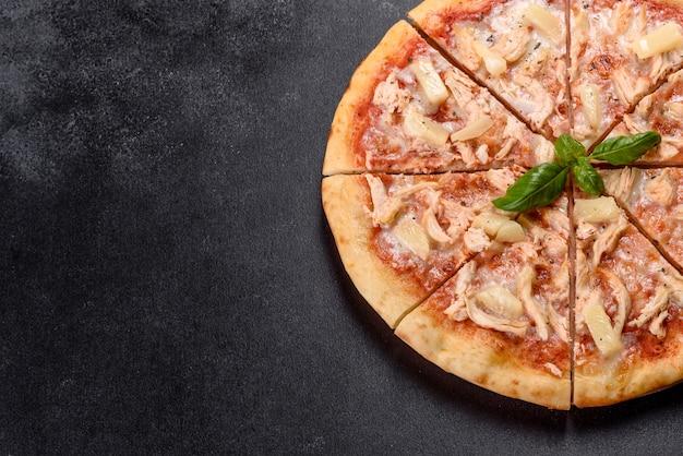 Gustosa pizza fresca al forno con pomodori, formaggio e ananas su uno sfondo di cemento scuro