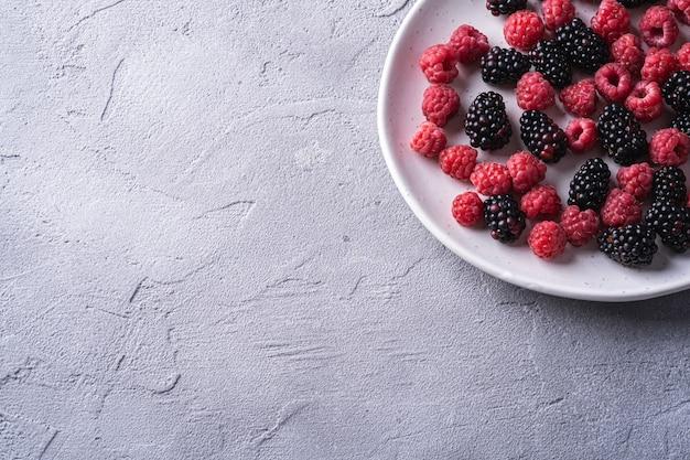 Gustosi lamponi maturi freschi e bacche di mora nel piatto, cibo sano frutta sulla tavola di cemento di pietra, spazio della copia di vista di angolo