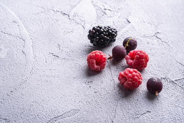 Gustoso lampone maturo fresco, mora, uva spina e ribes rosso bacche, cibo sano frutta sulla pietra tavolo in cemento, vista angolare macro spazio di copia